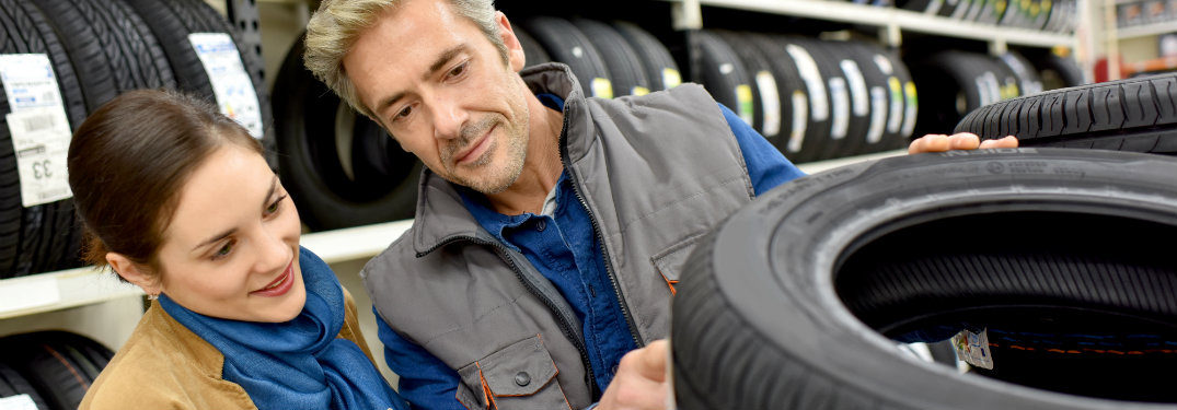 man and woman looking at the tread on a tire in a store