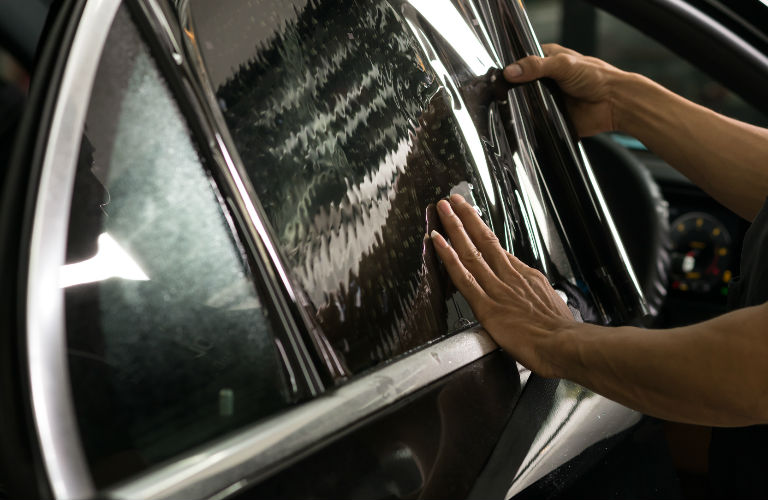 person putting tint on a side window