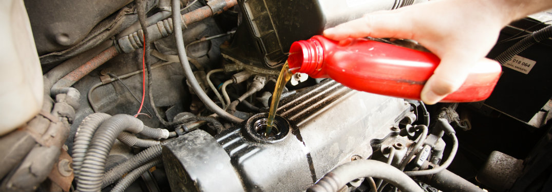 oil being poured into an engine from a red container