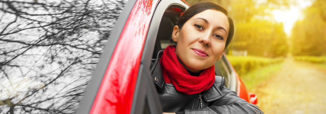 woman in a red car with her head out the window