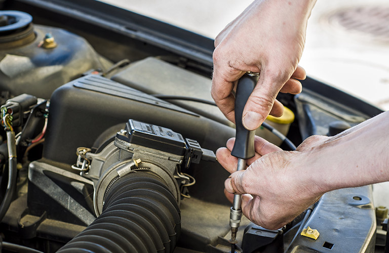 Pair of hands uses a screwdriver to tighten a screw in a a car engine.