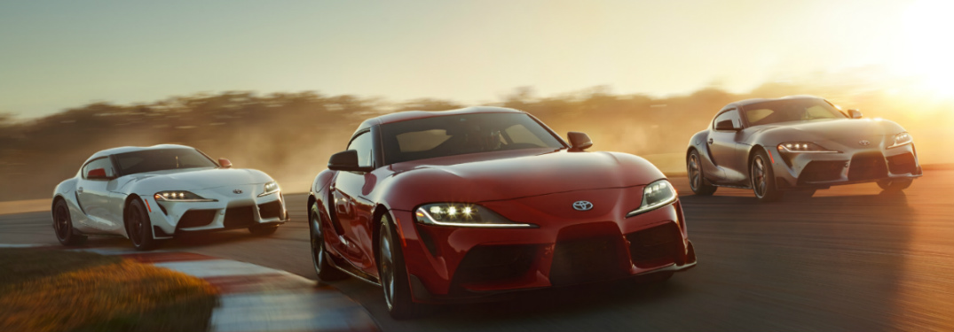 Three 2020 Toyota Supra sports cars cruise around a corner on a track at sunset.
