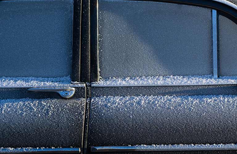 The side of a car is covered in frost, ice, and light snow.