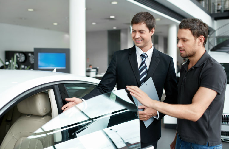 A salesman assists a customer with a used vehicle.