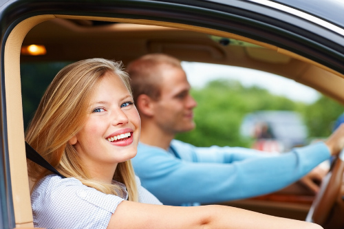 Happy young blonde woman rides in the passenger seat of a car.