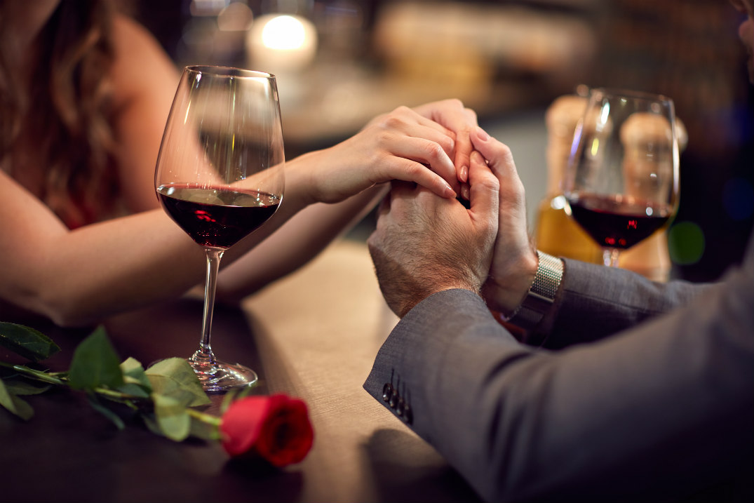 A man and woman's hands are clasped across a table. A red rose and two glasses of red wine are next to them.