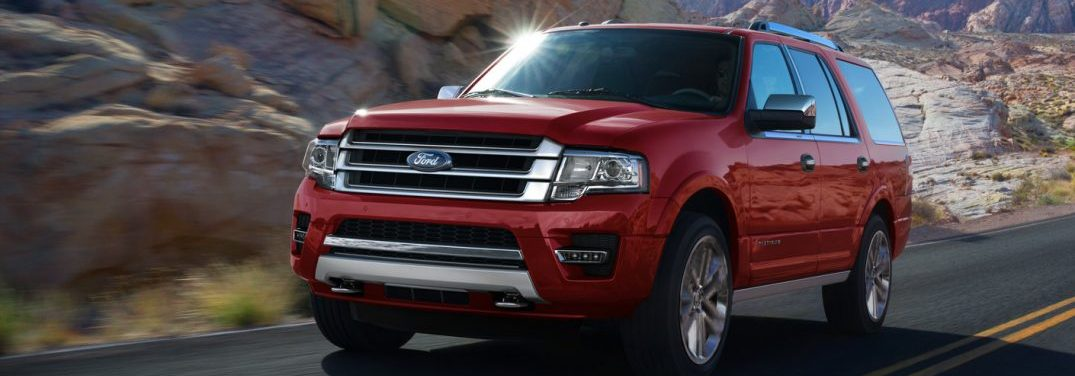 Red 2016 Ford Expedition drives down a desert highway.