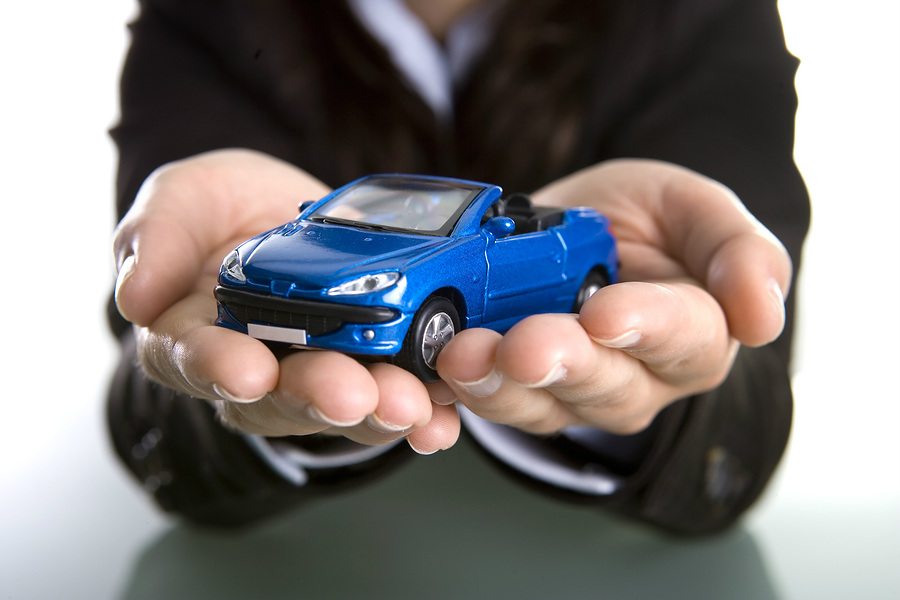 A businesswoman proffers a blue toy car in her outstretched hands. Take it. It's yours.