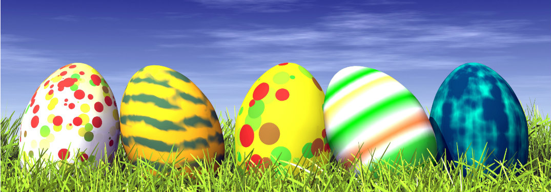 Four colored and patterend eggs sit on vibrant green grass with a blue sky behind.