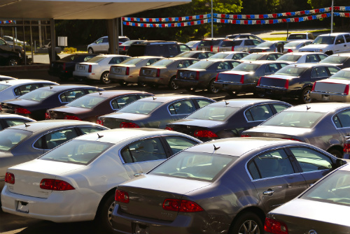 Rows of cars lined up at a car lot on a sunny day.