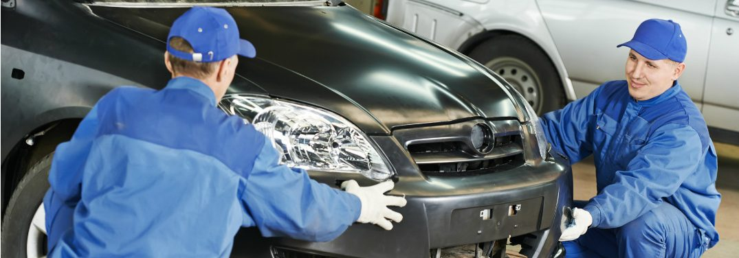 Two repairmen dressed in blue put a new bumper on the front of a car in the service shop.