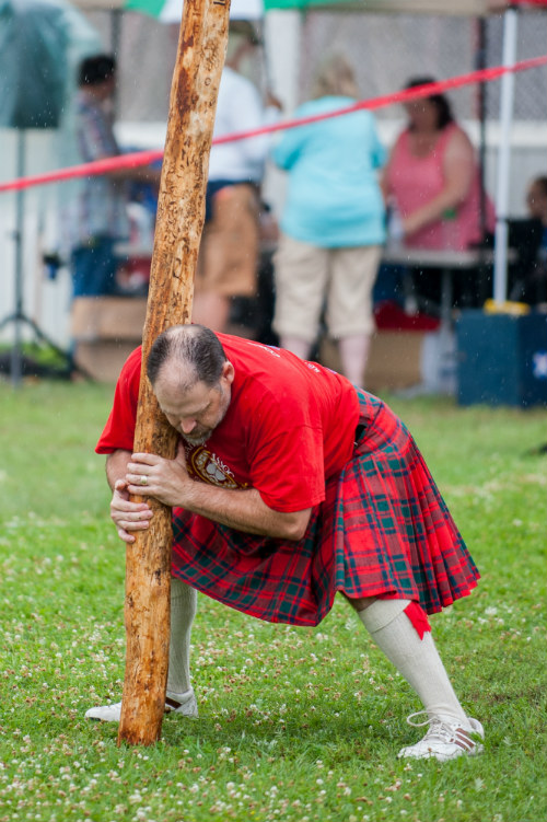 A burly, balding man wearing a kilt shoves a large stick into the green earth in some kind of strange Celtic tradition.