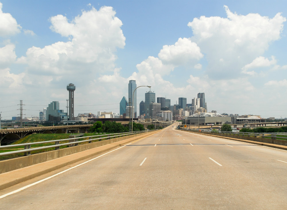 A deserted highway leads to downtown Austin TX. The skyline of Austin TX is visible.
