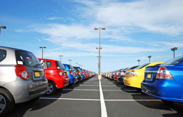 View between rows of multi-colored vehicles at a car lot under a bright blue sky with a few wispy clouds.