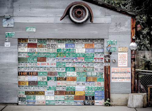 A variety of old license plates artistically attached to a garage door to make a multi-colored collage.