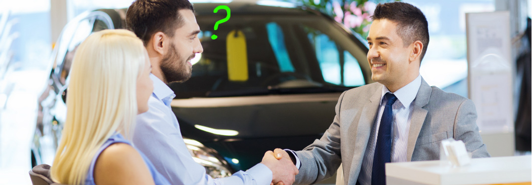 Salesman shakes the hand of a man who sits beside a woman, with a car in the background. A green question mark floats in front of the man's face, indicating something in unresolved in his mind.