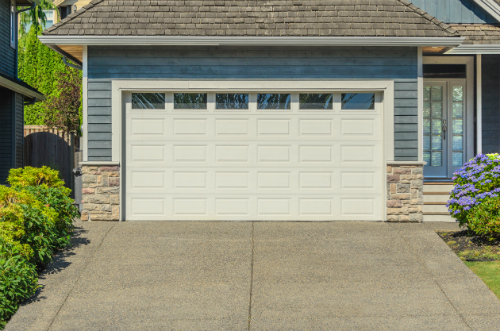 A two-car garage sits with its door closed at the top of a suburban driveway. One can't help but wonder: should I put one car in there, or two?