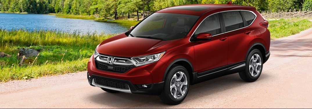 Red 2019 Honda CR-V drives along a mountain road with a blue lake beneath it. Exterior front/side angled view.