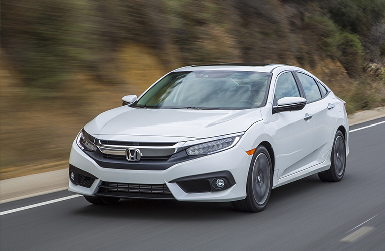 White 2018 Honda Civic drives on a highway. Exterior front/side angled view.