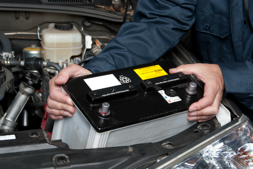 A man lifts a vehicle battery out of the vehicle.