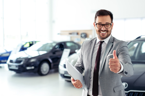 "A grinning salesman in glasses gives the ""thumbs up"" while standing in front of some cars in a showroom."