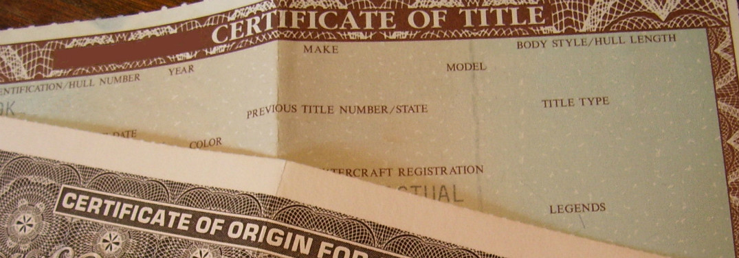 A vehicle Title certificate lays underneath a Certificate of Origin for a Vehicle.