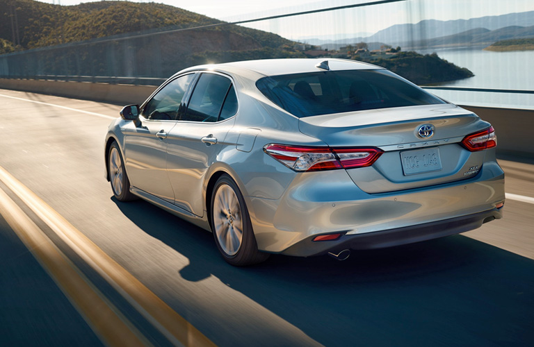 Silver 2019 Toyota Camry cruises down a highway, going over a bridge that looks like its in California.