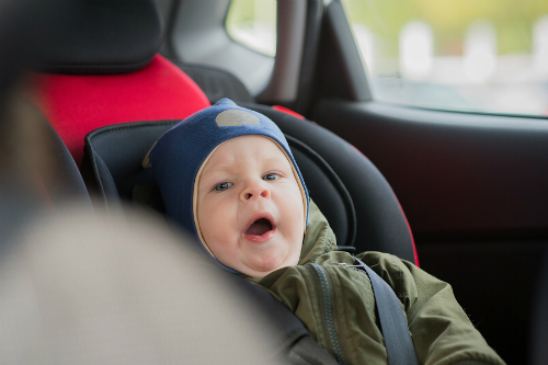 A yawning baby appears securely strapped into a stage two car seat, although unfortunately he is not rear-facing.