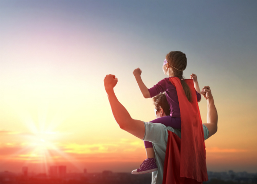 "A father and son wear red capes and make ""strong man"" flex gestures towards the setting sun. The boy is perched on the father's shoulders."