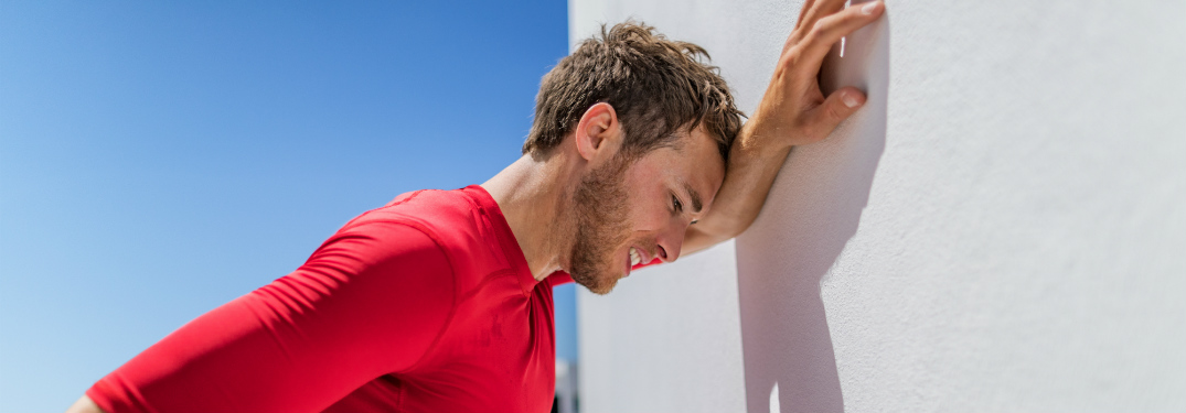 A tired, hot man in a red shirt leans against the wall. He may be battling heat exhaustion, but we hope he's okay.
