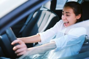 A young woman screams in terror while trying to drive, but maintains a smile on her face.