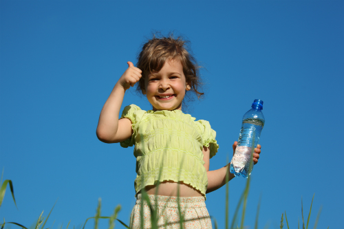 A small girl holds a bottle of water under the hot sun and gives a thumbs up- she's feeling good because she's well-hydrated.