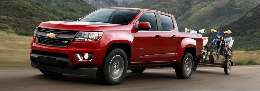 Red Chevrolet Colorado drives up a road amidst mountains, towing a trailer carrying motorbikes.