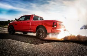 A red 2017 RAM 1500 squeals and smokes its tires as it drives away down a road.