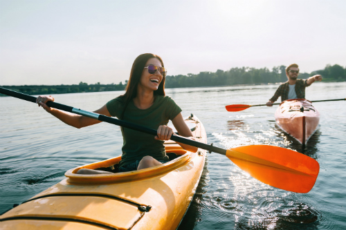 Two humans happily kayak on a body of water that shares the same planet with Austin, TX.