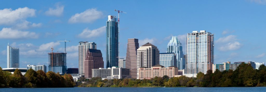 A view of the Austin, TX skyline with a blue size behind.