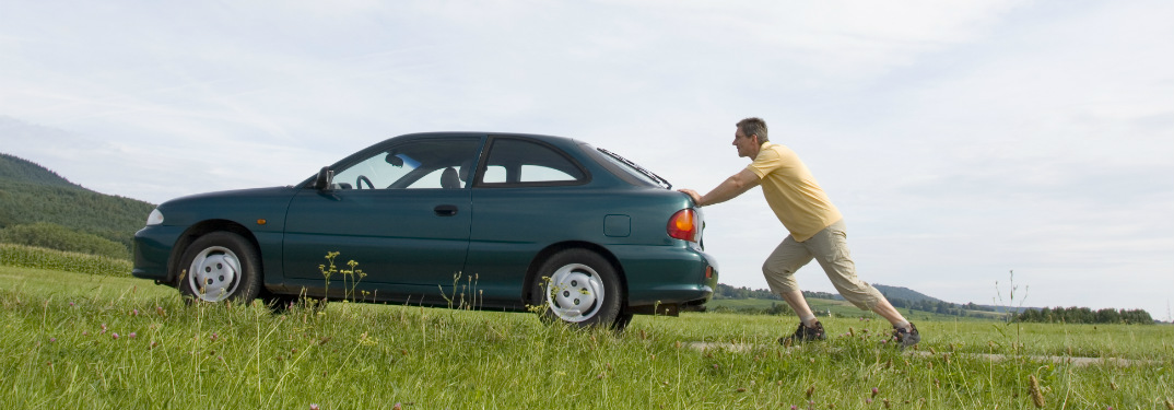 A man in a yellow shirt pushes a green car up a countryside road.