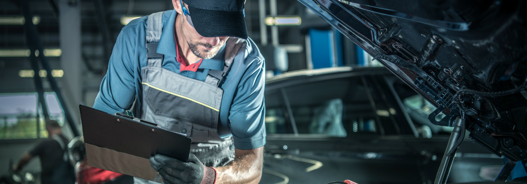 A mechanic holds a clipboard and looks under the hood of a car, presumably at a carbon-soaked direct injection engine.