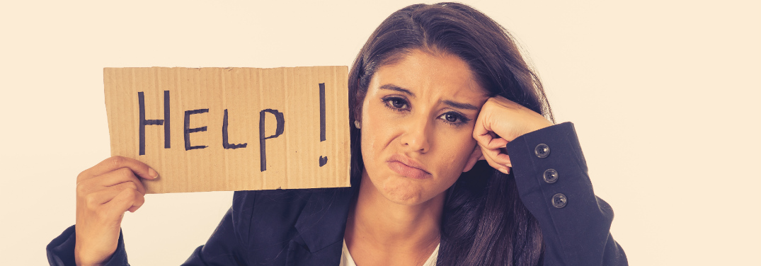 """A bummed-out looking woman holds up a cardboard sign with the word, """"Help!"""" written on it."""