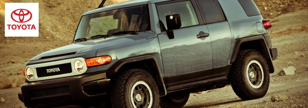 A green 2014 Toyota FJ Cruiser drives along rugged earth with a Toyota logo in the upper lefthand corner.