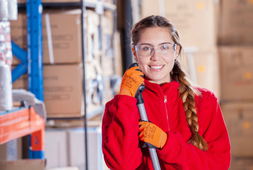 Worker in a warehouse smiling at camera while taking a short break
