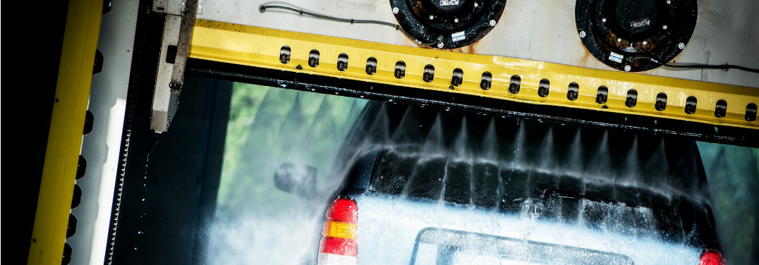 A car smushes through a car wash as a yellow bar sprays down on top of it.