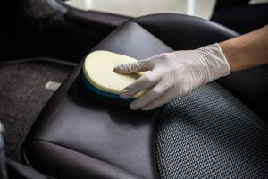 Gloved hand scrubbing leather car seat with sponge