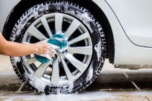 Hand holding sponge and cleaning car wheels with soap