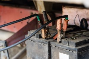 Rusty jumper cables on a battery
