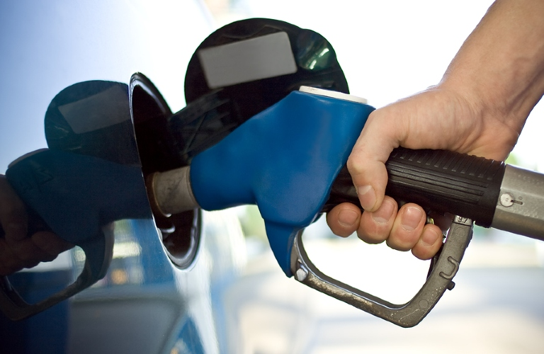 A hand holds a fuel pump in the gas tank of their car.