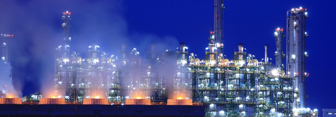 Skyline of an oil refinery at twilight, looking like the backdrop of a Sega Genesis game.