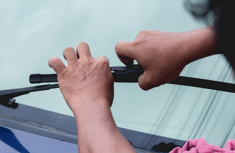 A person replaces the windshield wiper on a vehicle.