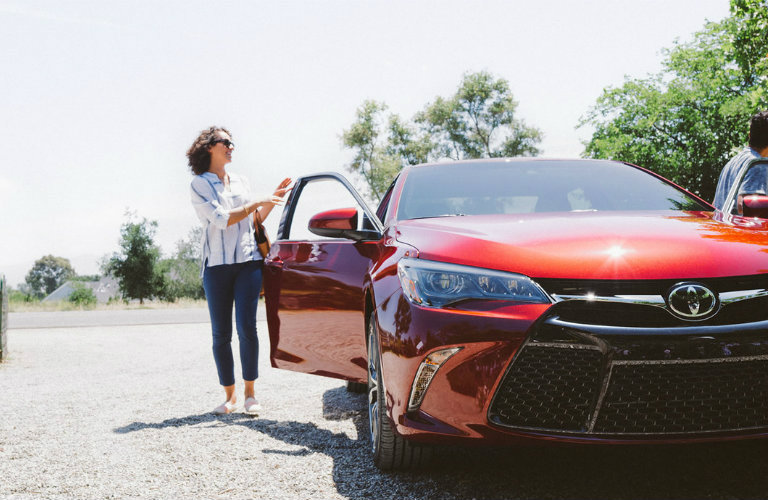 Woman opens the door of a red 2020 Toyota Camry parked on a sunny day.