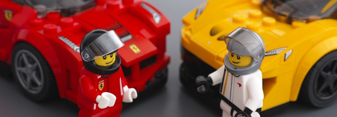Two lego drivers discuss their lego cars which are parked behind them